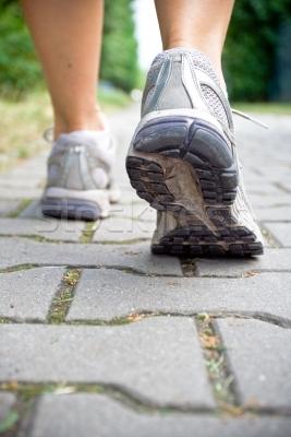 721700_stock-photo-woman-walking-on-sidewalk-recreation-concept